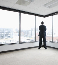 140894224-business-man-looking-out-corner-office-gettyimages